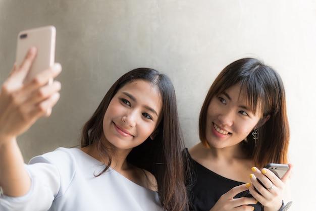 Junges asiatisches mädchen zwei, das handy verwendet, um sich selfie