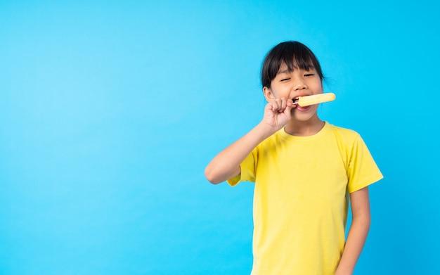 Junges asiatisches mädchenkind, das eiscreme isst und lustiges auf blau bekanntgibt