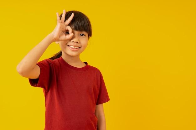 Junges asiatisches mädchenkind im roten hemd, das okayzeichen mit der hand auf dem auge schaut durch finger macht