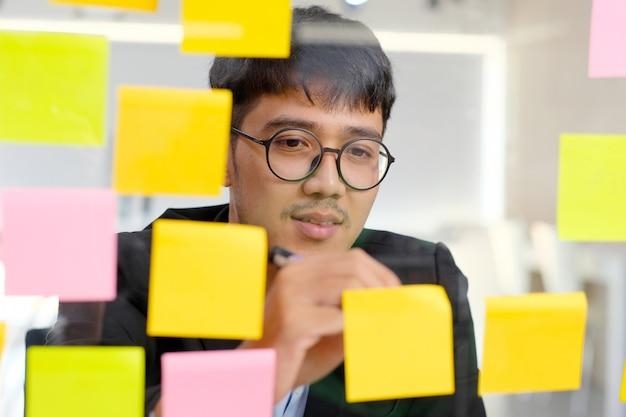 Junges asiatisches mannschreiben auf klebriger anmerkung im büro, geschäft, das kreative ideen gedanklich löst