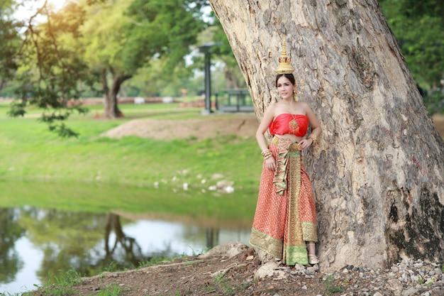 Junges asiatisches modemädchen, das thailändisches traditionelles kostüm mit schönheitsgesicht trägt