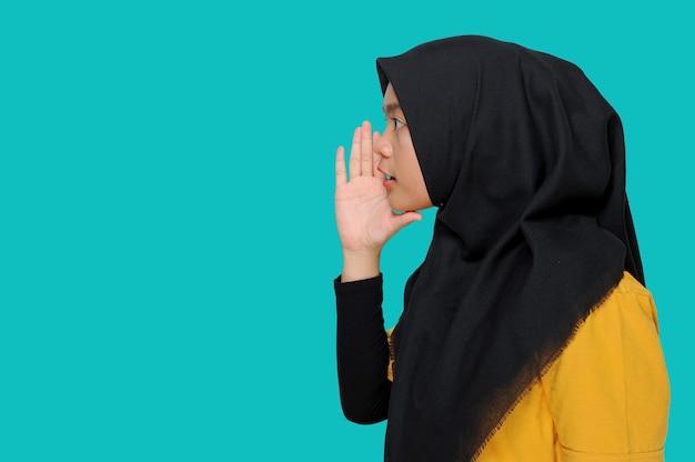 Junges asiatisches muslimisches mädchen, das auf blau flüstert