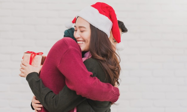Junges asiatisches paar, das einander eine geschenkbox während weihnachten gibt