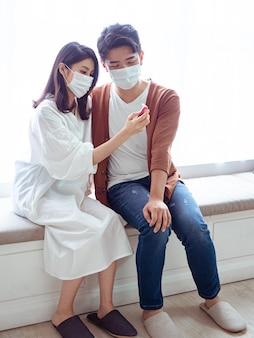 Junges asiatisches paar, das eine chirurgische maske trägt und ein ohrthermometer verwendet