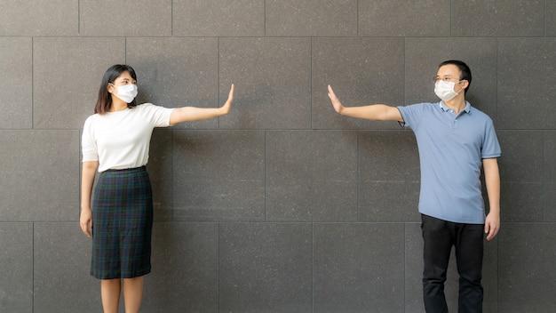Junges asiatisches paar, das gesichtsmasken trägt, die im freien gegen die wand für soziale distanzierung für infektionsrisiko und krankheitsprävention covid-19 treffen und stehen.