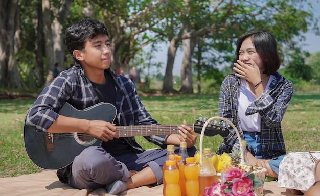 Junges asiatisches paar, das im urlaub im park lacht und gitarre spielt