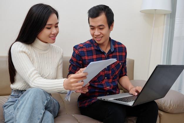 Junges asiatisches paar, das informationen aus einem dokument in ein formular auf einem laptop eingibt, um staatliche dienste zu erhalten?