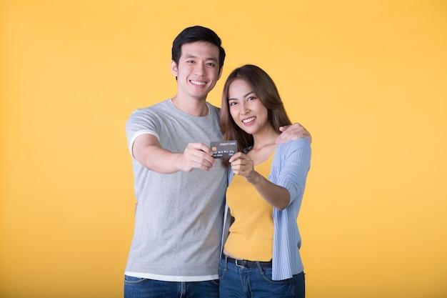 Junges asiatisches paar, das kreditkarte lokalisiert auf gelber wand zeigt