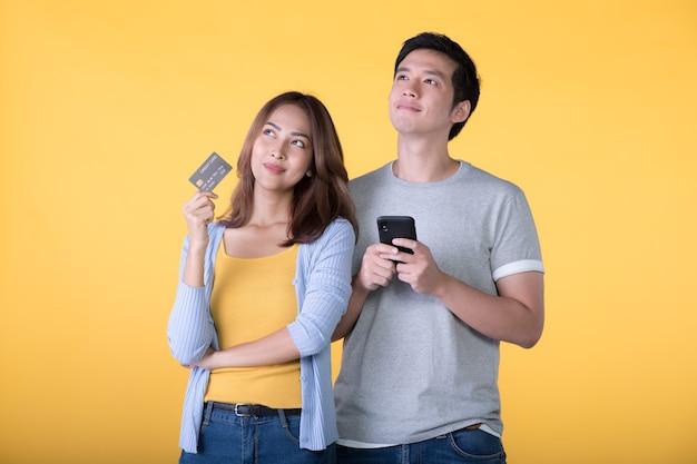 Junges asiatisches paar, das kreditkarte und smartphone beim aufschauen lokalisiert auf gelber wand hält