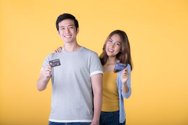 Junges asiatisches paar, das kreditkarten lokalisiert auf gelber wand zeigt