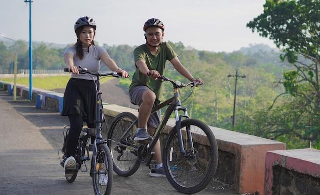 Junges asiatisches paar, das sich nach der fahrt mit dem fahrrad ausruht