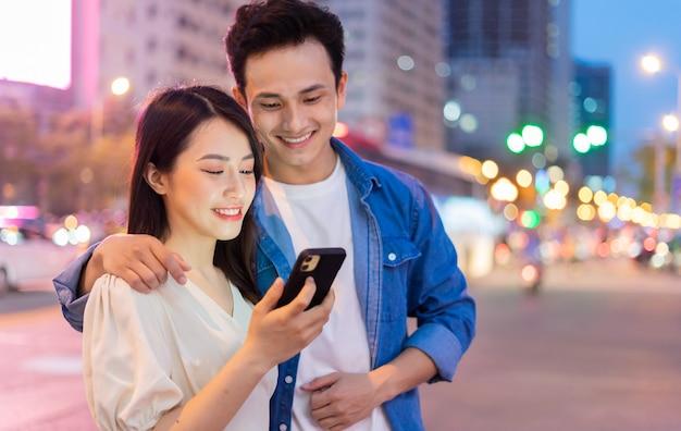 Junges asiatisches paar, das smartphone zusammen auf der straße in der nacht verwendet