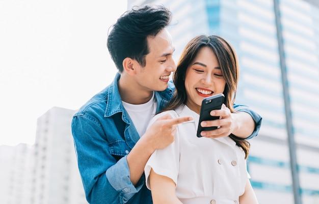 Junges asiatisches paar, das smartphone zusammen auf der straße verwendet