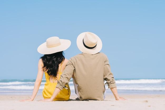 Junges asiatisches paar, das sommerferien am strand genießt