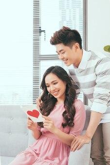 Junges asiatisches paar der liebe, das grußkarte des valentinsgrußes hält