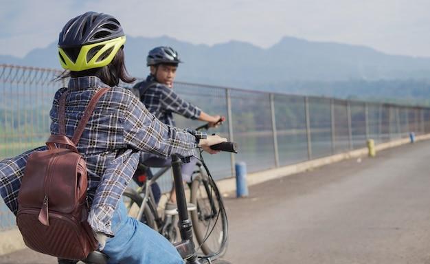 Junges asiatisches paar fährt zusammen fahrrad zur arbeit
