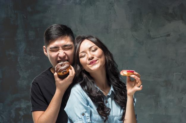 Junges asiatisches paar genießt das essen des süßen bunten donuts auf grauem studiohintergrund