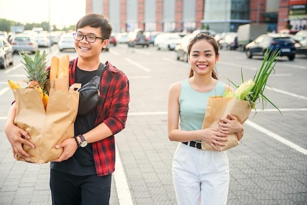 Junges asiatisches paar in der liebe, die in der stadt nach dem einkaufen geht