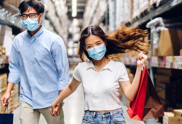 Junges asiatisches paar in quarantäne für coronavirus, das einen chirurgischen gesichtsschutz mit sozialer distanzierung trägt und einkaufstüten im store.covid19 und neues normales konzept hält