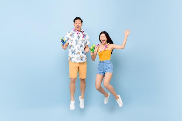 Junges asiatisches paar in sommeroutfits mit wasserpistolen, die für songkran festival in thailand und südostasien springen