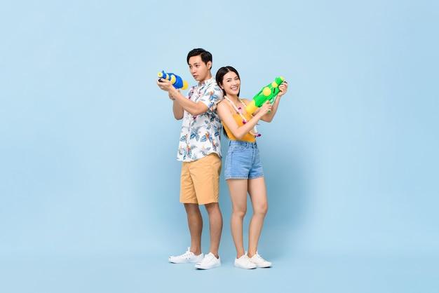 Junges asiatisches paar in sommeroutfits mit wasserpistolen für songkran festival in thailand und südostasien