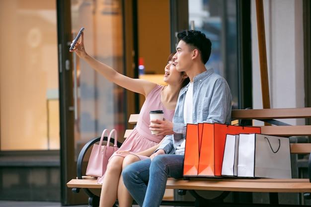 Junges asiatisches paar mit einkaufstüten