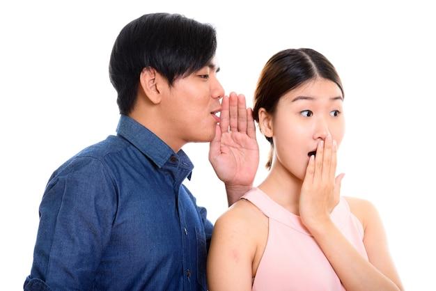 Junges asiatisches paar mit mann, der zu frau flüstert, die schockiert schaut
