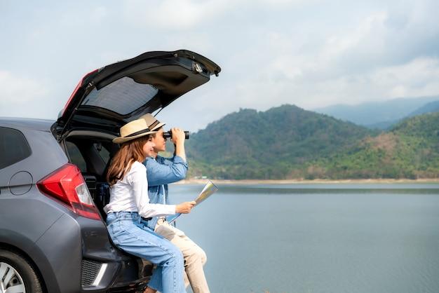 Junges asiatisches paar mit manntourist, der durch fernglas schaut, während seine lächelnde freundin nahe mit karte auf auto sitzt