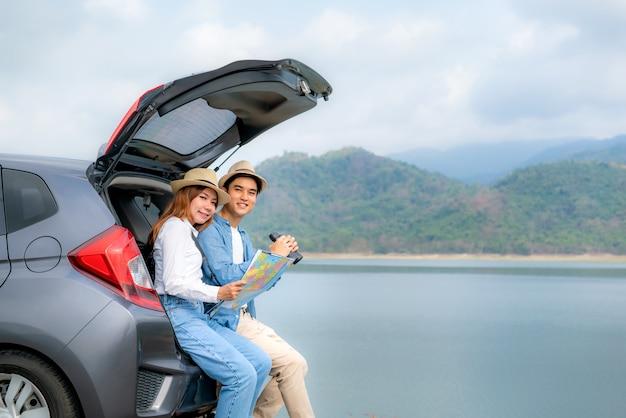 Junges asiatisches paar mit manntourist, der fernglas mit lächelnder freundin hält, die nahe mit karte auf autokofferraum sitzt und die kamera im ländlichen feld betrachtet