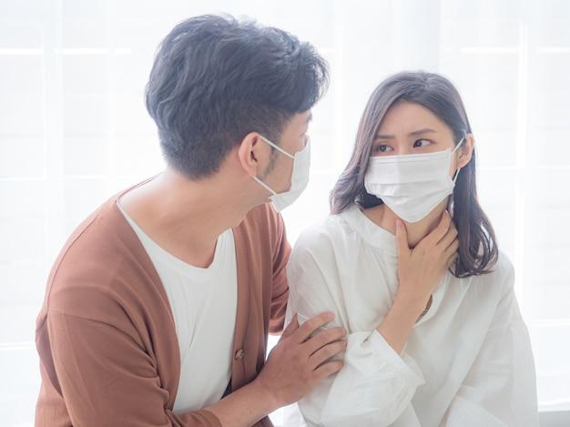 Junges asiatisches paar mit mundschutz auf weißem hintergrund