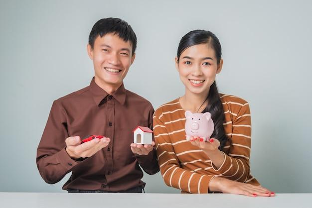 Junges asiatisches paar mit sparschwein und spielzeughaus und auto