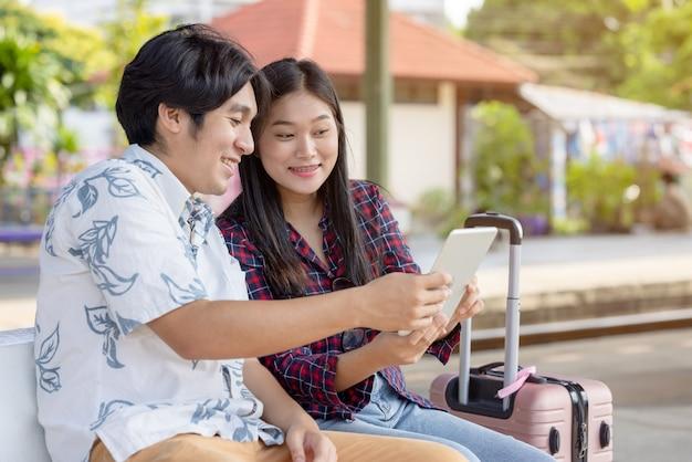 Junges asiatisches paar rucksacktourist mit tablet für die suche nach zielreise am bahnhof
