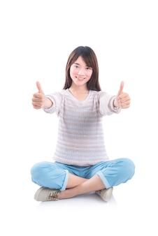 Junges asiatisches schönes mädchen, das auf dem boden sitzt und daumen oben über weißem hintergrund zeigt