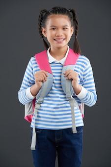 Junges asiatisches schulmädchen, das mit rucksack aufwirft