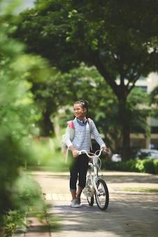 Junges asiatisches schulmädchen mit rucksack und fahrrad gehend durch park