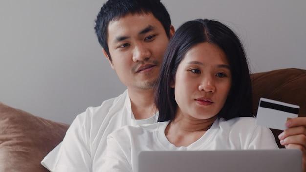Junges asiatisches schwangeres paaron-line-einkaufen zu hause. mutter und vati, die unter verwendung des kaufenden babyproduktes der laptoptechnologie und der kreditkarte beim auf sofa im wohnzimmer zu hause liegen glücklich sich fühlen.
