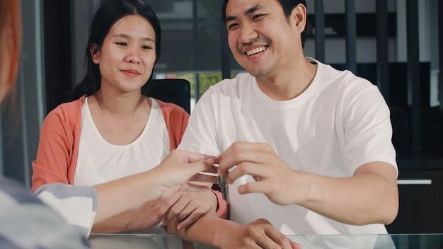 Junges asiatisches schwangeres paarzeichen-vertragsdokumente zu hause, japanische familie, die mit immobilienfinanzberater sich berät, neues haus und händeschütteln mit dem vermittler kauft, der schlüssel im wohnzimmer gibt.
