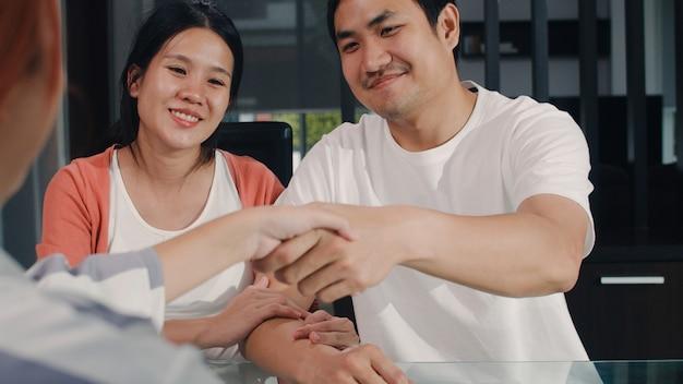 Junges asiatisches schwangeres paarzeichen-vertragsdokumente zu hause, japanische familie, die sich morgens mit immobilienfinanzberater, kaufendem neuem haus und händeschütteln mit vermittler im wohnzimmer berät.