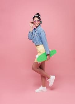 Junges asiatisches teenager-mädchen, das skateboard mit dem tragen der drahtlosen kopfhörer hält, die musik auf rosa wand hören.