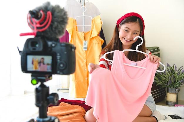 Junges asiatisches vlogger-bloggerinterview der schönheit mit professionellem dslr-digitalkamerafilmvideo