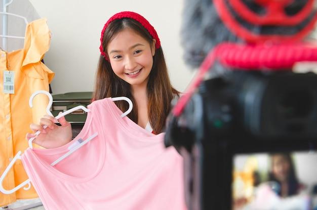 Junges asiatisches vlogger-bloggerinterview der schönheit mit professioneller dslr-digitalkamera