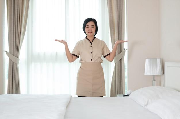 Junges asiatisches zimmermädchen im hotelzimmer
