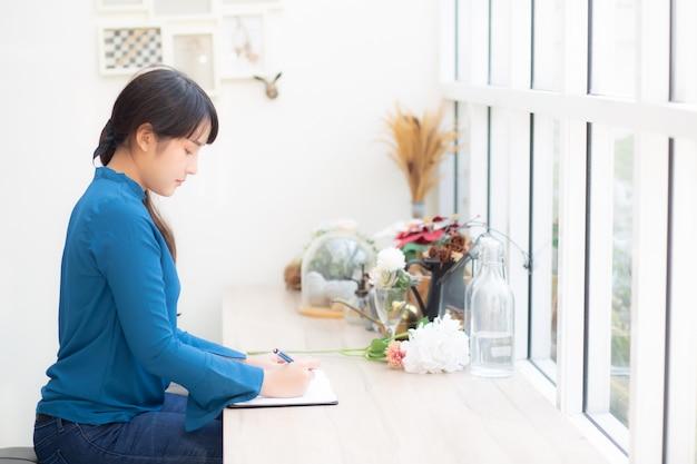 Junges asien-verfasserinschreiben des schönen porträts auf notizbuch oder tagebuch mit glücklichem