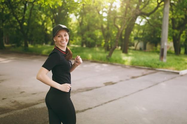 Junges athletisches lächelndes schönes brünettes mädchen in schwarzer uniform und mützentraining, sportübungen und laufen, rückblick auf den weg im stadtpark im freien