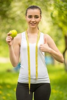 Junges athletisches mädchen, das grünen apfel nach training isst.