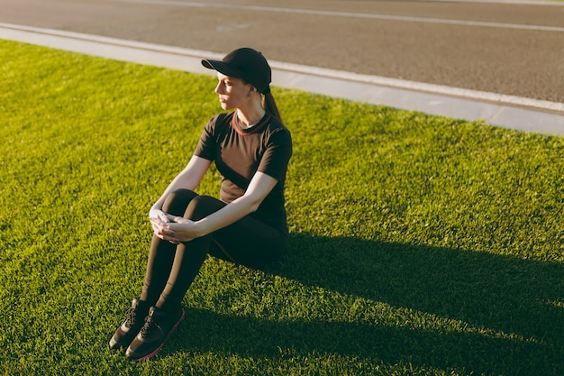 Junges athletisches mädchen in schwarzer uniform, mütze sitzt entspannend auf grünem rasen im golfplatzpark nach sportübungen, läuft an sonnigen sommertagen im freien. fitness, gesundes lifestyle-konzept.