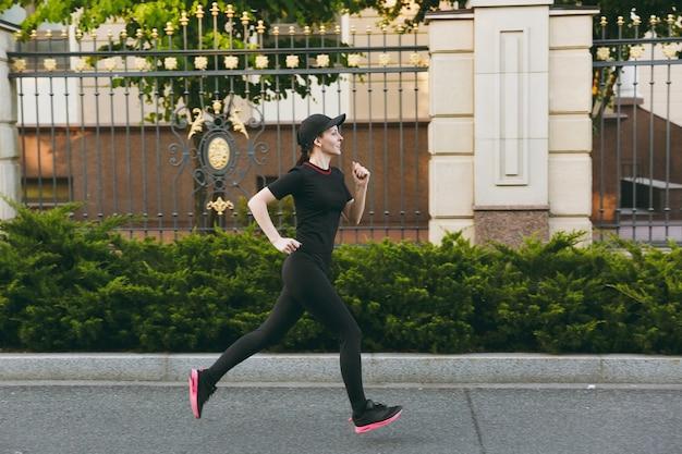 Junges athletisches mädchen in schwarzer uniform und mützentraining, sportübungen, laufen, blick direkt auf den weg im stadtpark im freien an sonnigen frühlings- oder sommertagen. fitness, gesundes lifestyle-konzept.