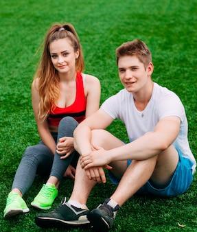 Junges athletisches paar, das auf dem gras sitzt
