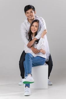 Junges attraktives asiatisches paar, das weißes hemd und schleier trägt und händchen hält, sitzt und lächelt dagegen