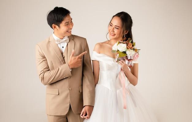 Junges attraktives asiatisches paar, mann, der beige anzug trägt, frau, die weißes hochzeitskleid trägt, das zusammen händchen haltend steht. konzept für die fotografie vor der hochzeit.